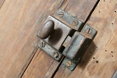 Cupboard Latch. Latch on a 140 year old cupboard.  The timber is Rimu, native to New Zealand.  The latch and screws are a little rusty Stock Photos