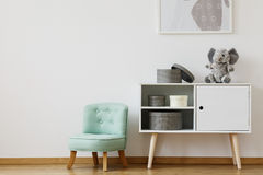 Cupboard and mint chair. Bright cupboard standing next to mint chair for children royalty free stock images