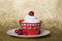 Cupcake με την κρέμα και τα βακκίνια στο κόκκινο υπόβαθρο Χριστουγέννων Στοκ Εικόνες