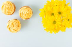 Cupcake με τη γλυκιά κίτρινη διακόσμηση κρέμας στο sauser και την ανθοδέσμη του κίτρινου χρυσάνθεμου στο φλυτζάνι γυαλιών Επίπεδο Στοκ εικόνα με δικαίωμα ελεύθερης χρήσης