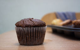 Cupcake. The chocolate cupcake in the liner on the table Royalty Free Stock Images