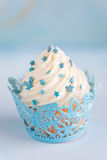 Cupcake. With a swirl of vanilla buttercream frosting and blue decor Stock Photo