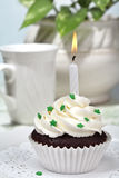 Cupcake. Chocolate Cupcake with buttercream frosting decorated with green sprinkles and a Birthday candle in a cake and coffee party setting stock photo