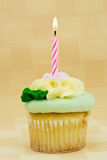 Cupcake. With one candle burning in front of a yellow textured background. Icing is butter cream.  is yellow Stock Photography