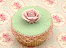 Cupcake. Two cupcakes decorated with pink flower on a tablecloth Royalty Free Stock Images