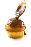 Cupcake. A muffin being topped with liquid chocolate which is flowing down from a brazen spoon stock image