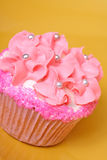 Cupcake. Pink themed cupcake with frosting flowers decorated with silver balls and pink sprinkles royalty free stock photography