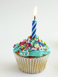 Cupcake. Blue themed cupcake with flickering candle candy sprinkles and frosting stock photos