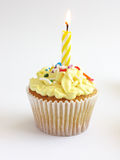 Cupcake. Yellow themed cupcake with flickering candle yellow frosting decorated with multi colored sprinkles stock photos