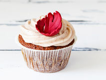 Cupcake with a autumn leaf decoration. One cupcake with a red autumn leaf marzipan decoration on white vintage wooden background Royalty Free Stock Photo