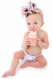 Cupcake Baby. Adorable 10 month old baby girl eating pink frosting cupcake over white background Stock Image