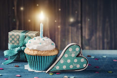 Cupcake with birthday candle. And gift box Stock Photography