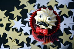 Cupcake with black mustache, red bow tie and white cream on top. Movember cancer awareness in November month. Movember campaign against prostate cancer. Gold stock images