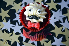 Cupcake with black mustache, red bow tie and white cream on top. Movember cancer awareness in November month. Movember campaign against prostate cancer. Gold stock photos