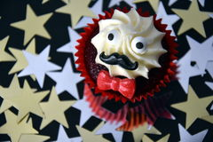 Cupcake with black mustache, red bow tie and white cream on top. Movember cancer awareness in November month. Movember campaign against prostate cancer. Gold royalty free stock images