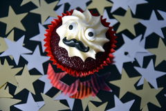 Cupcake with black mustache and white cream on top. Movember cancer awareness in November month. Movember campaign against prostate cancer. Gold and silver stock images