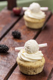 Cupcake with blackberries. Jam cupcake with mascarpone cream cheese topping strawberry on table in studio Royalty Free Stock Images