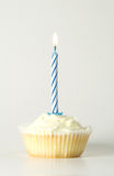 Cupcake with blue candle. Iced cupcake with single blue birthday candle Stock Image