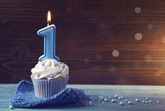Cupcake with a blue candle. For first birthday stock images
