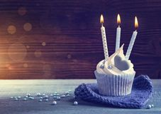 Cupcake with a blue candles. For birthday stock photography