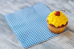 Cupcake on blue checkered napkin. Stock Photo