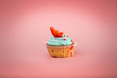 Cupcake with blue cream and fresh strawberry over pink backgroun Royalty Free Stock Photo