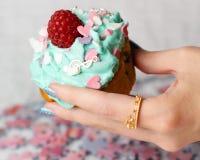Cupcake. Blue delicious hearts cream hand holding nailpolish ring food sweets cake Stock Image