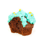 Cupcake with blue frosting of which one bite taken Royalty Free Stock Images