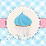 Cupcake with blue icing on blue gingham background Stock Photos