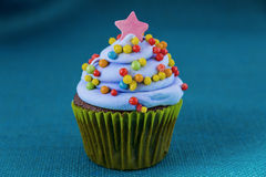 Cupcake with blueberry frosting and colorful sprinkles Royalty Free Stock Images