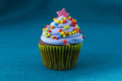 Cupcake with blueberry frosting and colorful sprinkles Stock Photography