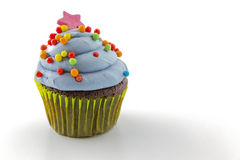 Cupcake with blueberry frosting and colorful sprinkles Stock Photos