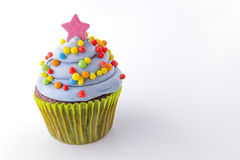 Cupcake with blueberry frosting and colorful sprinkles Stock Photo