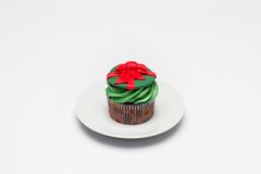 Cupcake with butter cream icing on the saucer. Christmas Royalty Free Stock Photos