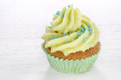 Cupcake with butter cream and turquoise sprinkles Stock Images