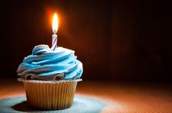 Cupcake with buttercream and burning candle on wooden table against dark background with copy space. Stock Photo