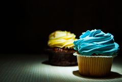 Cupcake with buttercream on wooden table against dark background with copy space. Stock Image