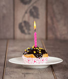 Cupcake with candle. Cupcake with multi colored spinkles and candle on top Stock Photography