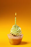 Cupcake with candle isolated on orange Royalty Free Stock Photo