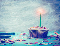Cupcake with candle on retro turquoise background, toned. Royalty Free Stock Photography