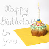 Cupcake with a candle, and text happy birthday Royalty Free Stock Photos