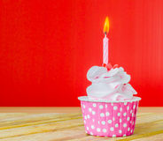 Cupcake. With candle on top on color background Stock Image