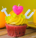 Cupcake. With candle on wood table Royalty Free Stock Images