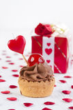 Cupcake with cherry in front of gift box Royalty Free Stock Photos