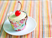 Cupcake with cherry on top. A cupcake with vanilla frosting and cherry on top Stock Photos