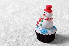 Cupcake Christmas snowman on white snow Royalty Free Stock Photography