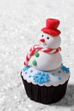Cupcake Christmas snowman on white snow Royalty Free Stock Image
