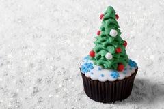 Cupcake Christmas tree on white snow. Royalty Free Stock Photo