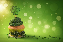 Cupcake with clover cakepick. On a wooden background stock photography