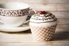 Cupcake and coffee cup. Studio shot of a tasty cupcake and a coffee cup on wood background Stock Images